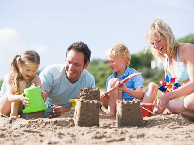 Children making sand castles with parents